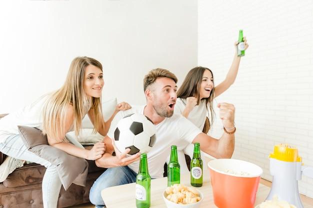 Gente feliz gritando viendo fútbol en casa