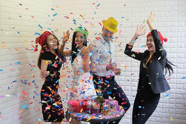 Gente feliz del grupo empresarial en el sombrero de santa que se divierte para la fiesta de navidad de la celebridad.