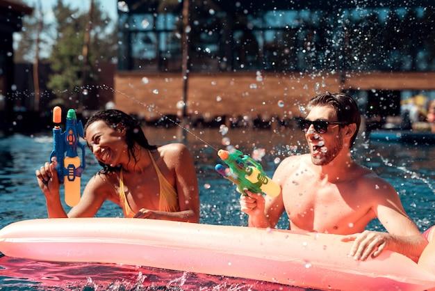 Gente feliz jugando juntos con agua colorida