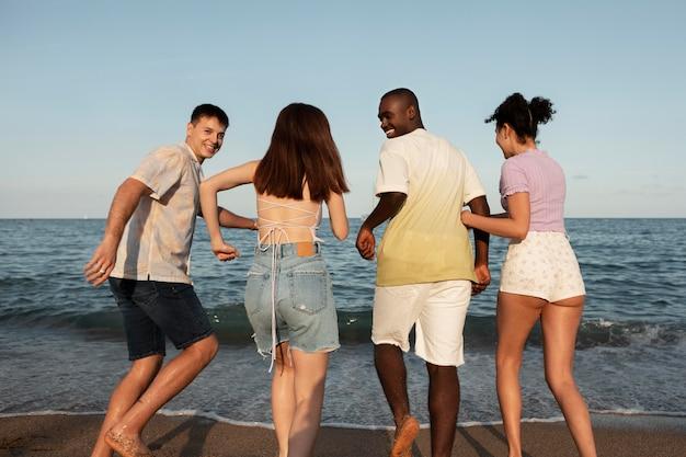 Gente feliz en la playa de tiro medio