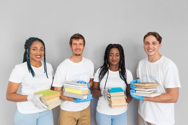 Gente feliz sosteniendo un montón de libros para donarlos.