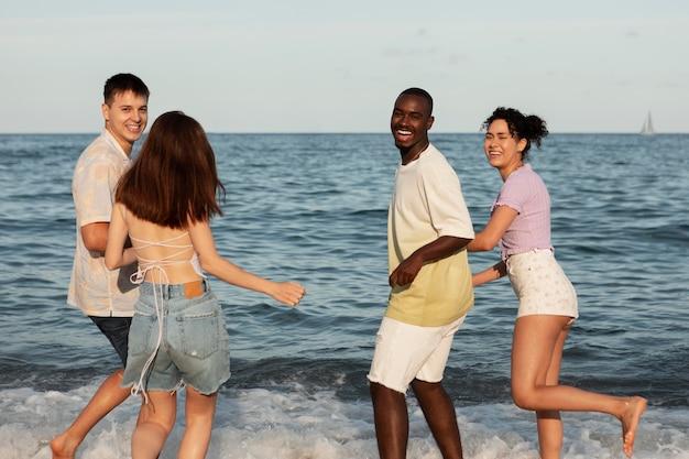 Gente feliz en tiro medio junto al mar