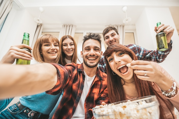 Gente feliz tomando una selfie en la fiesta en casa. mejores amigos que se divierten en interiores bebiendo cerveza. conocer gente viajando concepto