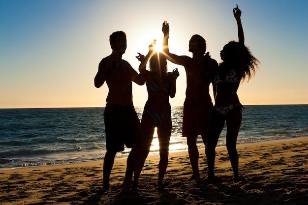 Gente de fiesta en la playa con bebidas