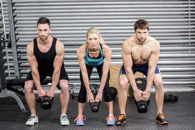 Gente en forma levantando pesas en el gimnasio