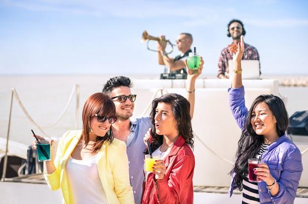 Gente funky bailando música y divirtiéndose juntos en la playa, fiesta después de la hora