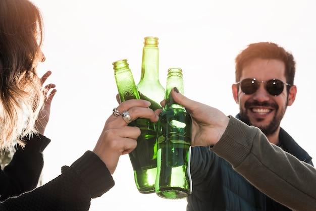 La gente golpea botellas de cerveza