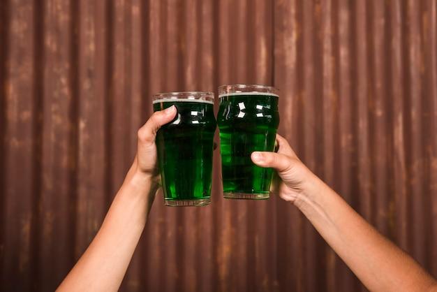 La gente golpea copas de bebida verde