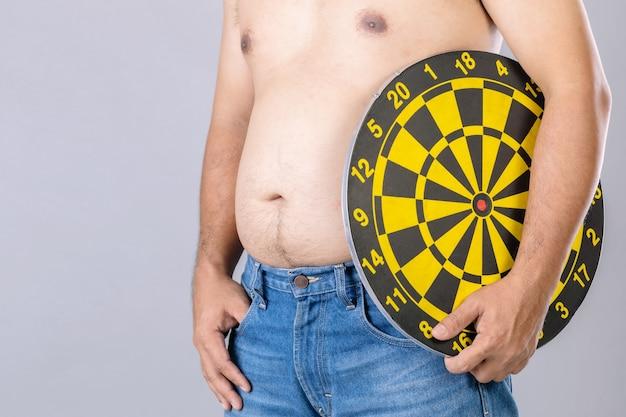 Gente gorda que sostiene el tablero de dardos amarillo redondo al lado de su posición del vientre. objetivo del concepto de pérdida de peso.