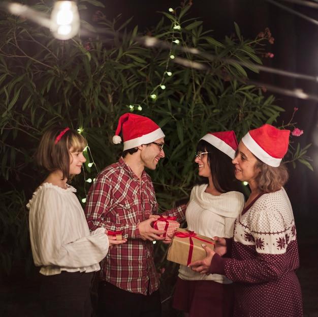 Gente con gorros de santa intercambiando regalos.