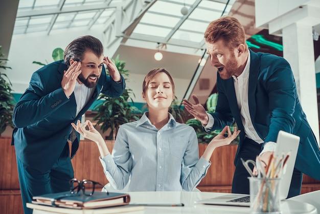 La gente grita al trabajador meditando en la oficina.