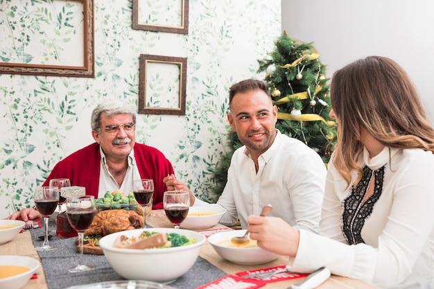 Gente hablando en mesa festiva.