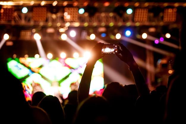 La gente hace fotos con teléfonos inteligentes en concierto de rock para compartir el momento con amigos en las redes sociales