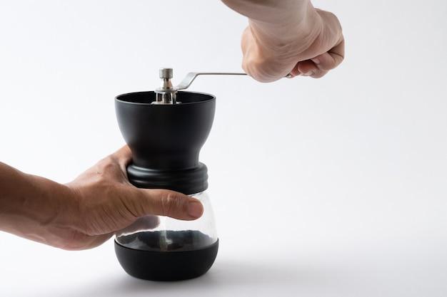 La gente hace girar el café con la mano. amoladora de mano.