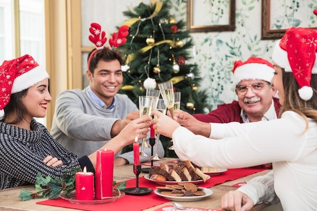 Gente haciendo copas de champán en la mesa navideña