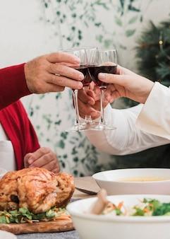 Gente haciendo copas de vino en mesa festiva.