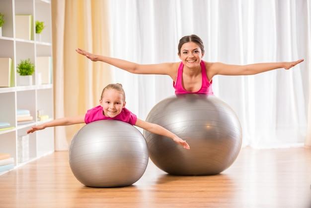 La gente está haciendo ejercicios físicos en la pelota de fitness en casa.