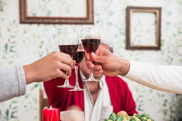 Gente haciendo sonar las copas en la mesa festiva