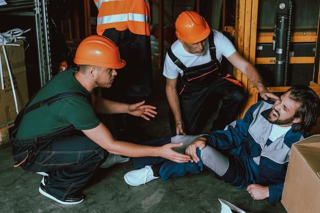 La gente de hardhats se preocupa por el compañero de trabajo que se acuesta en el piso