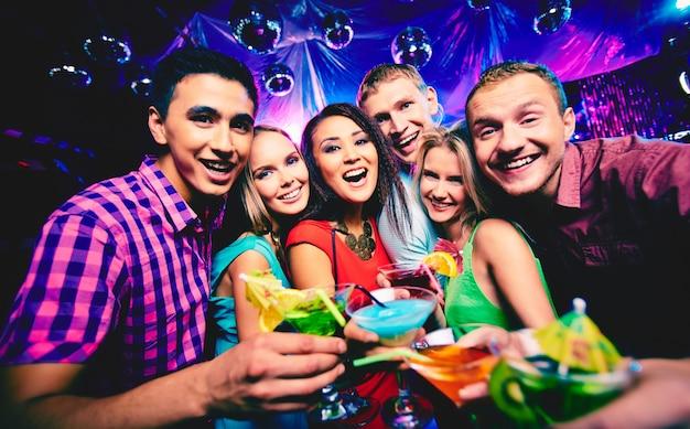 Gente joven brindando en la discoteca
