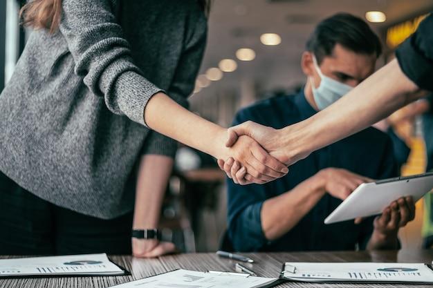 Gente joven dándose la mano en la oficina