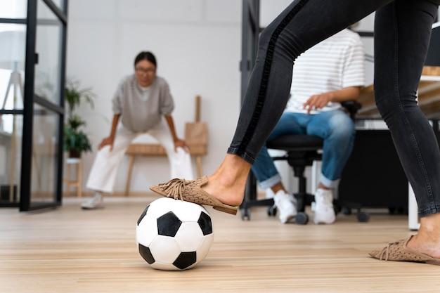 Gente joven jugando con la pelota en la oficina