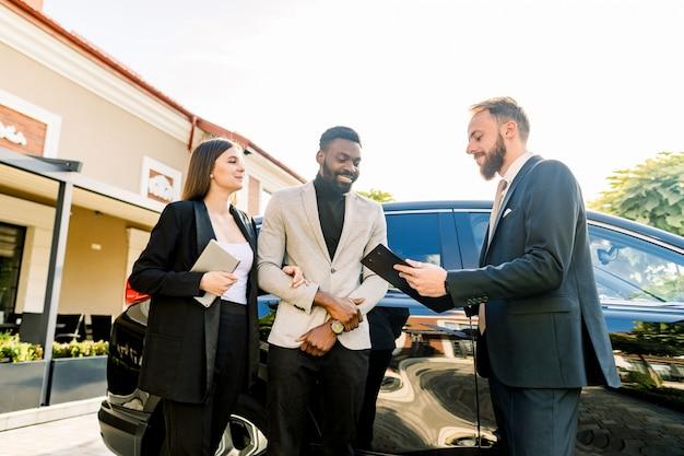 Gente joven pareja de negocios hombre africano y mujer caucásica de pie al aire libre en un servicio de alquiler de coches, hablando con el gerente de joven. concepto de auto servicio