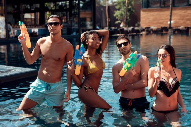 Gente joven sonriente en la piscina con pistolas de agua.