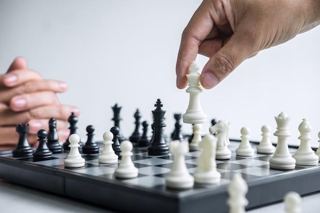 Gente jugando al ajedrez con peones blancos y negros