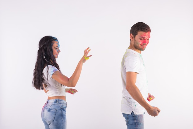Gente jugando con colores en el festival de holi en pared blanca