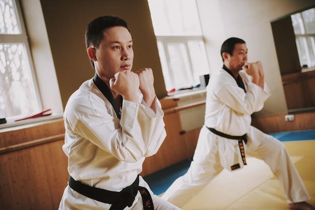 Gente en kimono blanco trabajando en bastidores con jiu jitsu.