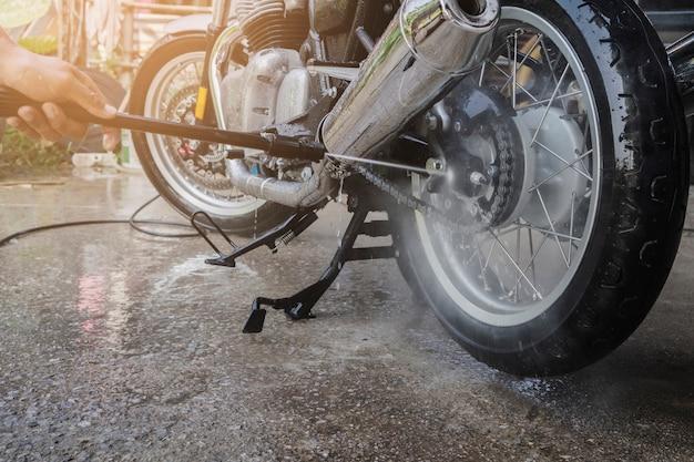 La gente lava la motocicleta de limpieza en casa