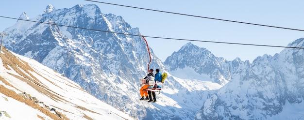 La gente está levantando en ascensor abierto en las montañas del cáucaso