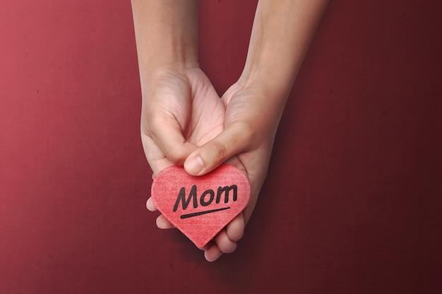 Gente mano sosteniendo corazón rojo con mensaje del día de la madre