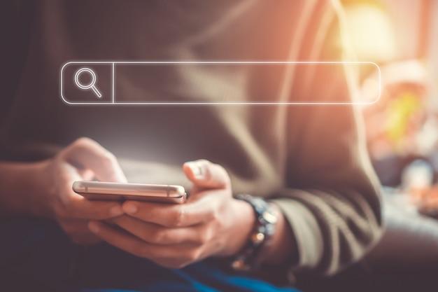 La gente de la mano mediante teléfono móvil o teléfono inteligente en busca de información en la web de la sociedad en línea de internet con el icono del cuadro de búsqueda.