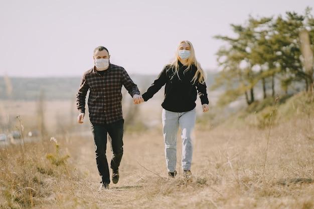 La gente en máscaras camina en un campo