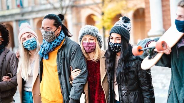 Gente milenial urbana caminando juntos usando mascarilla en el centro de la ciudad