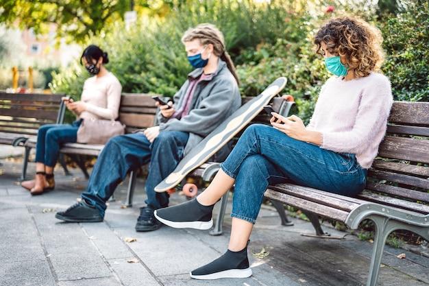 Gente milenial viendo videos en teléfonos inteligentes con máscara facial en la tercera ola de covid
