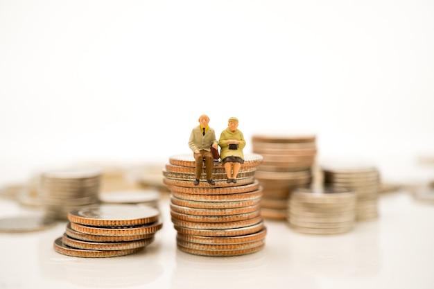 Gente miniatura, ancianos sentados en monedas de pila usando como retiro de trabajo