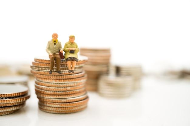 Gente miniatura, ancianos sentados en monedas de pila utilizando como concepto de retiro de trabajo