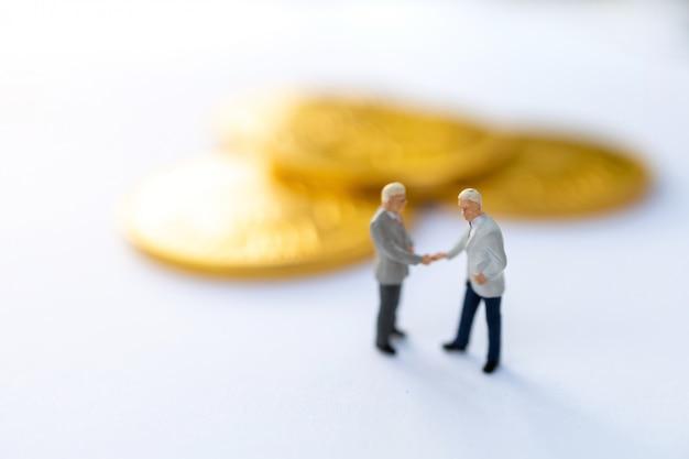 Gente miniatura: apretón de manos de empresarios con monedas de oro, crecimiento en concepto de negocio.
