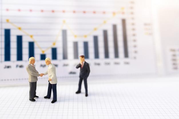 Gente miniatura: apretón de manos de hombres de negocios con gráfico de negocios, crecimiento en concepto de negocio.