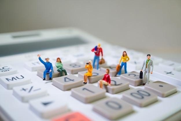 Gente miniatura en calculadora