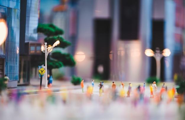 Gente en miniatura caminando por las calles, la gente se está moviendo a través del paso peatonal