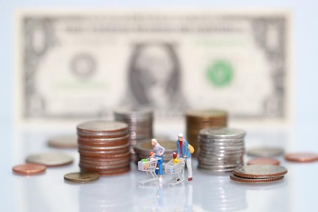 Gente en miniatura: comprador que camina al lado del dinero, negocios que usan como fondo