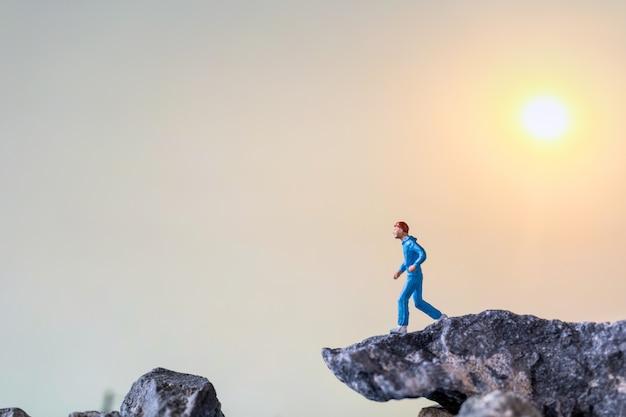 Gente en miniatura: corriendo por el acantilado de roca, conceptos de salud y estilo de vida