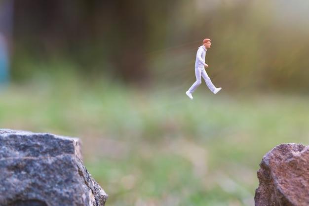 Gente en miniatura: corriendo en un acantilado de roca con fondo de naturaleza