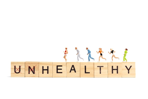 Gente en miniatura corriendo en bloque de letras de madera sobre fondo blanco concepto saludable.