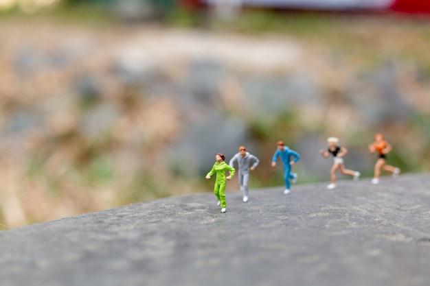 Gente miniatura corriendo en la roca
