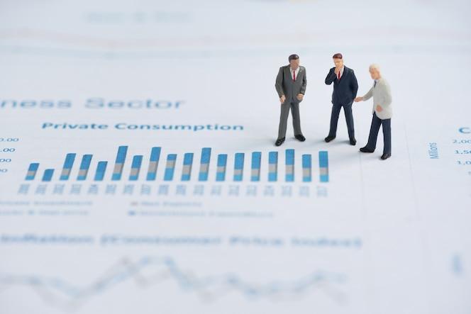 Gente miniatura de negocios en gráfico de negocios
